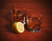Highball whiskey glass with ice and lemon. — Stock Photo
