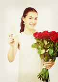Girl with bouquet of red roses and card in hand. — Stock Photo