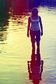 Lovely woman in jeans rolled in sea water. — Stock Photo