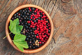 Bllack and red currant and green leaves in wooden bowl. — ストック写真