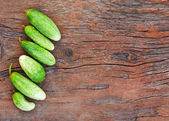 Juicy ripe green cucumbers on old wooden background. — Stock Photo