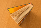 Book on wooden table viewed above — Stock Photo