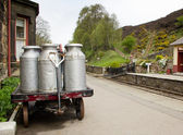 Milk churns in old railway station — Stock Photo