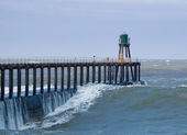 Whitby pier in ruwe zee — Stockfoto