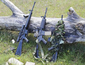 Military weapons for airsoft in a clearing near a wood — Stock Photo