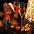 Santa Bear with a glass of champagne on background shining light - Stock Photo