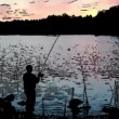 Stock Video: Nightly fishermcatches fish in lake