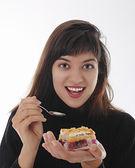 Lächelnd mädchen essen ein stück kuchen — Stockfoto