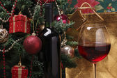 Glass of red wine on the and christmas tree — Stock Photo