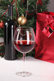Red wine, christmas tree and bag with gift — Stock Photo