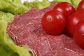 Tomatoes are on thin slices of salami and lettuce — Stock Photo