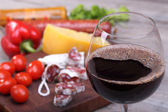 Red wine in the glass and food background — Stock Photo