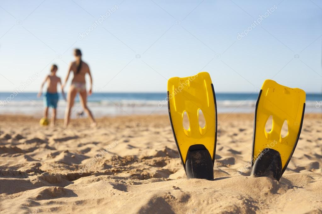 Children playing on the beach behind diver fins — Stock Photo #13920295