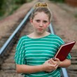 Stock Photo: Young adolescent girl with book on railroad tracks.