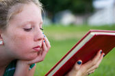 Young girl looking at book — Stock Photo