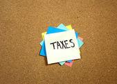 付箋メモおよびコルクのボード上の税金 — ストック写真