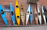 Many old time vintage kayaks stacked against the wall — Stock Photo