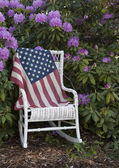 US Flag draped on a antique white wicker chair — Stock Photo