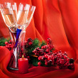 Stock Photo: Christmas card. Champagne, a branch of a fur-tree and a candle on a red background