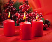 Christmas card. branch of a fur-tree and a candle on a red background — Stock Photo