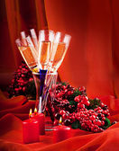 Christmas card. Champagne, a branch of a fur-tree and a candle on a red background — Stock Photo