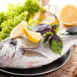 Fresh fish of dorado on a frying pan with a lemon and olive oil — Stock Photo