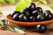 Black olives in a wooden plate and a rough board — Stock Photo