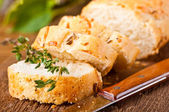Fresh bread and butter on a wooden board — Stock Photo