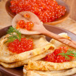 Pancakes with red caviar on wooden ware — Stock Photo #21261439