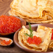 Pancakes with red caviar on wooden ware — Stock Photo #21262179