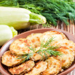 Green zucchini pancakes on a wooden old board — Stock Photo
