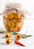 Bank of olives with pepper on a wooden board — Stock Photo