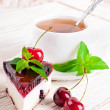 Cherry cheesecake with tea on a wooden table — Stock Photo
