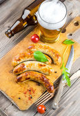 The Munich sausages with tomatoes and arugula — Stock Photo