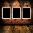 Empty frames in room against brick wall — Zdjęcie stockowe #12624693