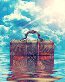 Treasure chest in water agaist cloudy sky — Stock Photo