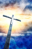 Cross in sunrays against cloudy sky — Stock Photo