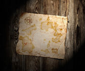 Old treasure map on wooden background — Stock Photo