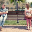 Young couple at quarrel on bench in park — Stock Photo