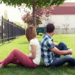 Young couple sitting outdoors on bench bored in relationship — Stok fotoğraf