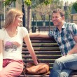 Young couple sitting on bench in park — Stock Photo