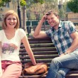 Stock Photo: Young couple sitting on bench in park