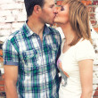 Couple kissing on brick wall background — Stockfoto