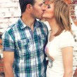 Stock Photo: Couple kissing on brick wall background