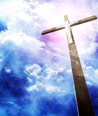 Cross in sunrays against cloudy sky — Stock Photo