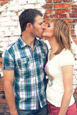 Couple kissing on brick wall background — Stock Photo