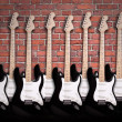 Electric guitars on brick wall — 图库照片