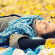 Young woman laying in autumn leaves — Stock Photo