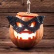 Stock Photo: Halloween pumpkin in mask on wooden background