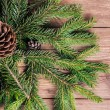 Christmas tree branches with bumps on wooden background — Stock Photo #34604455